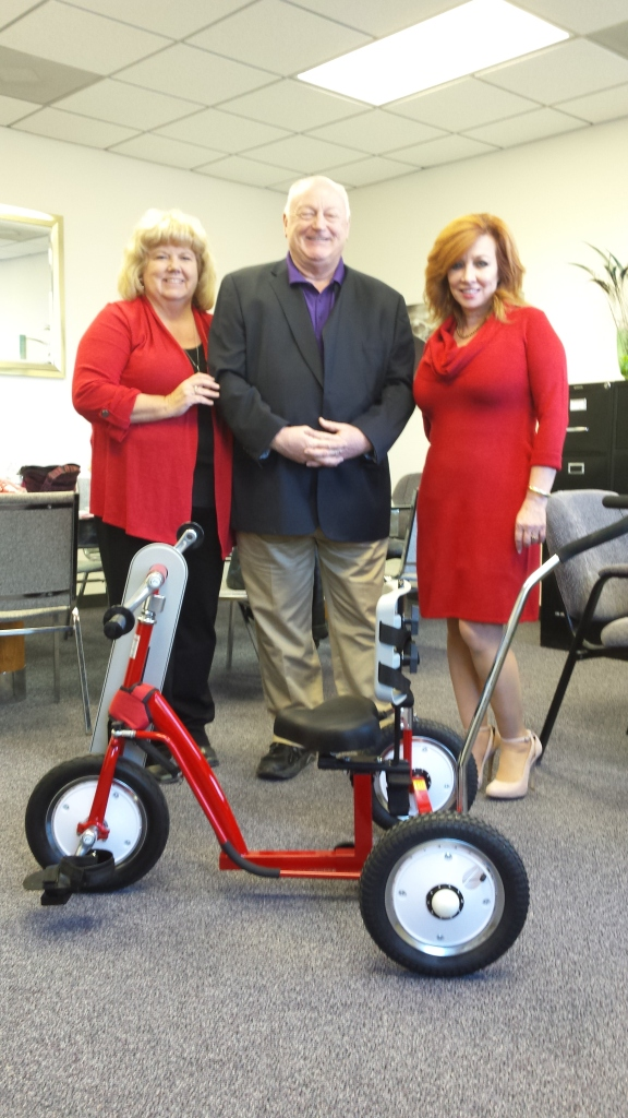 Admiring a child's trike that can be hand or foot operated are, from left to right: NOLA AMBUCS President Cindy Payton; NOLA AMBUCS Chairman of the Board Glenn Payton, and United Cerebral Palsy of New Orleans Interim Executive Director Kendra Nelson. The New Orleans Chapter of AMBUCS provides therapeutic tricycles to children with disabilities unable to ride traditional bikes. -- Photo Credit: Alex Gonzalez